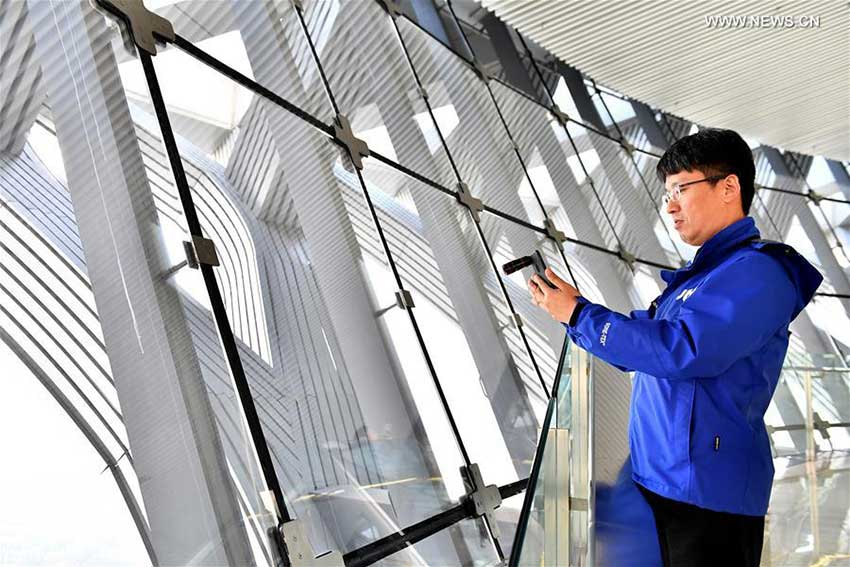 A journalist from Republic of Korea takes photos at the Olympic Tower in Beijing, capital of China, Oct. 12, 2017. The Press Center of the 19th National Congress of the Communist Party of China (CPC) organized a reporting tour along the Central Axis of Beijing on Thursday. Chinese and foreign reporters visited scenic attractions such as the Jingshan Park, Yongding Gate and the Olympic Tower. (Xinhua/Li Xin)