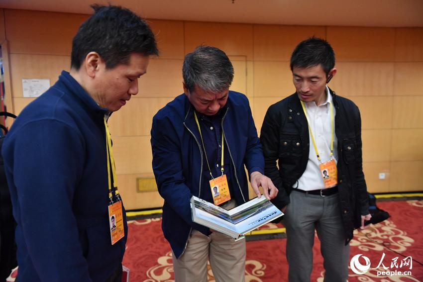 Journalists from China and abroad are attracted by the books displayed at the Press Center of the 19th National Congress of the CPC. The 19th CPC National Congress will convene on Oct. 18 in Beijing. (People's Daily Online Photo / Yu Kai)